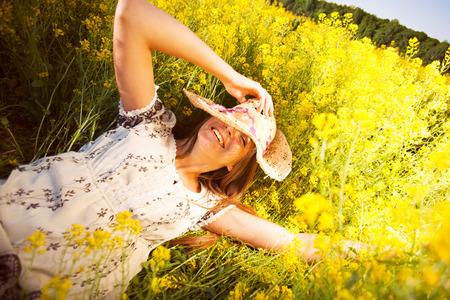Glückliche Frau unter gelben Wildblumen im Sommer liegen