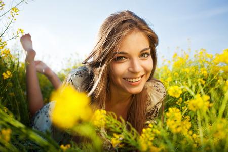 Cute happy girl lies among yellow wildflowers photo