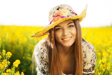 blithe: Happy woman in a hat of yellow wildflowers Stock Photo