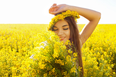 Beautiful happy girl with a bouquet of wildflowers photo
