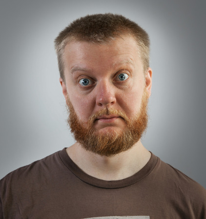 bulging eyes: Bearded man with bulging eyes in a brown t-shirt Stock Photo