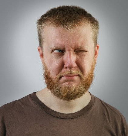 Redbeard man looking off to the side with one eye Stock Photo