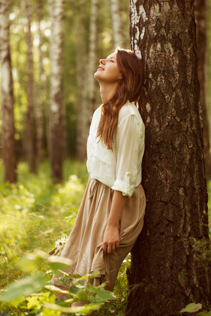 Beautiful woman leaning against birch and resting