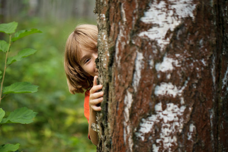 blithe: Playful boy peeking out from behind a tree trunk Stock Photo