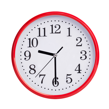 Half past nine on a red round clock face Stock Photo