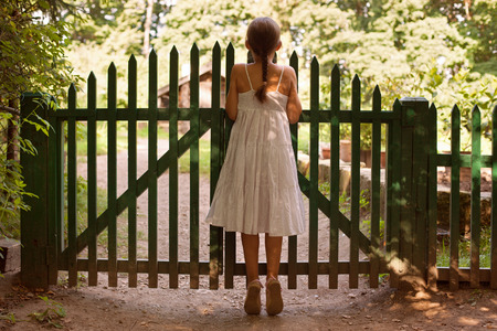 oversee: Little girl standing on tiptoes and looking over the fence Stock Photo