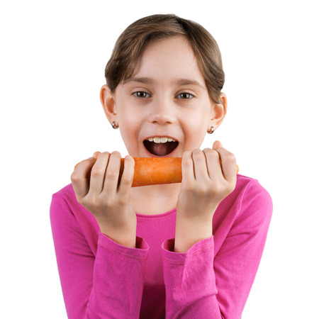 Happy little girl eating a large carrot photo