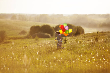 blessedness: Happy girl with balloons running on the field of dandelions