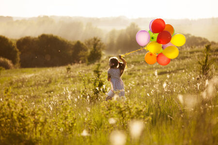weather balloon: Girl running on the field of dandelions with inflatable balls