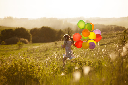 Happy little girl running across the field with balloons Stock Photo