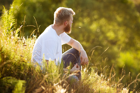 blessedness: Happy man sitting on the grass and looks into the distance