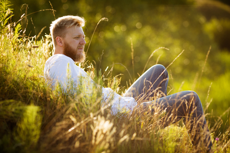 blessedness: Happy man lying on the grass and looks into the distance Stock Photo