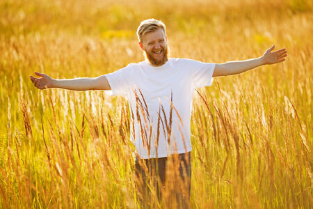 blessedness: Happy bearded man in a field of grass