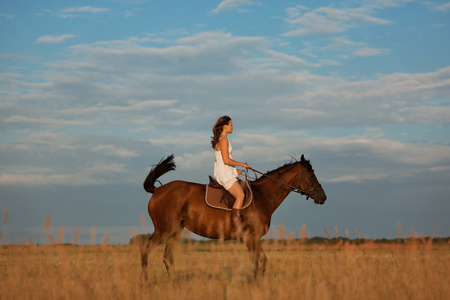 blessedness: Girl riding a horse in the field at sunset