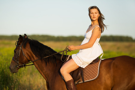 blessedness: Girl in white dress riding on a brown horse Stock Photo