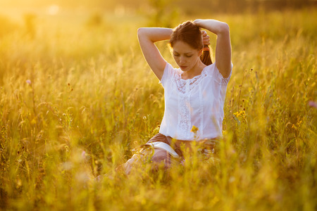 blessedness: Girl sitting on the grass reading a book Stock Photo