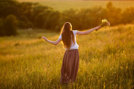 Happy young woman in the field with a bouquet of flowers Stock Photo