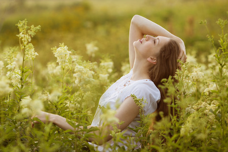 beatitude: Happy long-haired young woman of high wildflowers Stock Photo