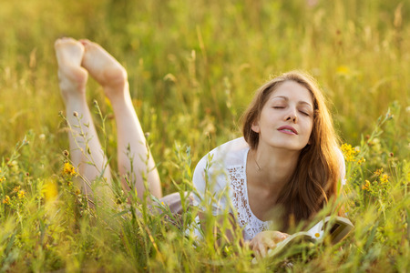 meditative: Happy girl with a book in the grass dreaming of something