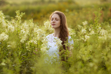 pacification: Happy young woman with eyes closed among the wildflowers