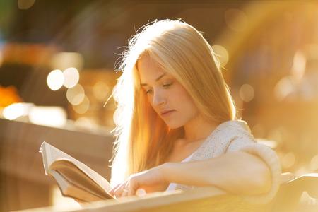 mujer leyendo libro: Feliz chica rubia sentada y leyendo un libro