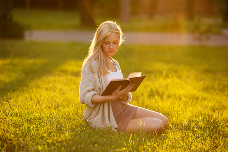 beatitude: Blonde girl sitting on the grass and reading a book Stock Photo