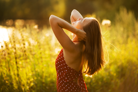 beatitude: Happy young woman in the rays of the evening sun