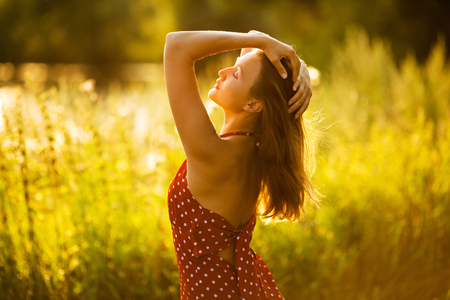 blessedness: Beautiful happy long-haired woman at sunset in the field