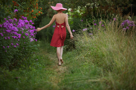 pacification: Woman in a hat walks among the beautiful flowers Stock Photo