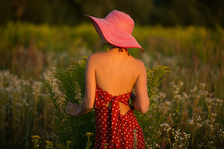 beatitude: Elegant beautiful woman in a hat among wildflowers at sunset