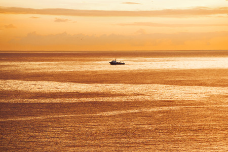 Marine vessel is sailing in the ocean at sunrise photo