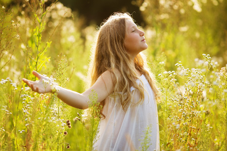 blessedness: Happy blonde girl in a dress of wildflowers Stock Photo