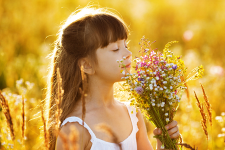wild flowers: Happy little girl with a bouquet of wild flowers