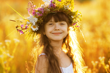 Happy cute girl wearing a wreath of wildflowers
