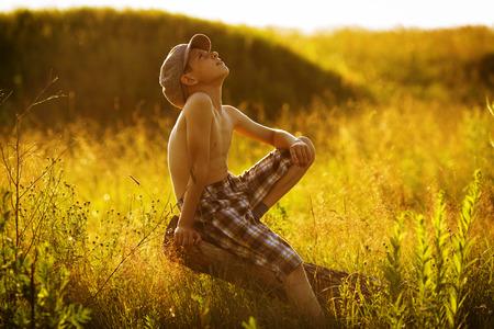 warmly: Happy boy sitting on driftwood and dreams