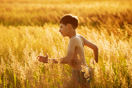 blessedness: Happy boy running in a field of high grass Stock Photo