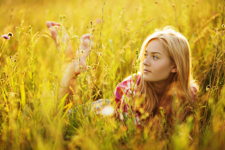 luxuriate: Happy barefoot girl in a field of grass and flowers Stock Photo