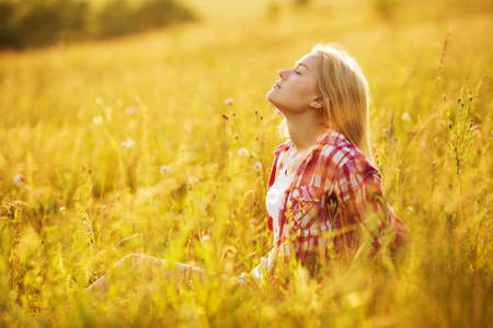 luxuriate: Happy girl with closed eyes in wildflowers