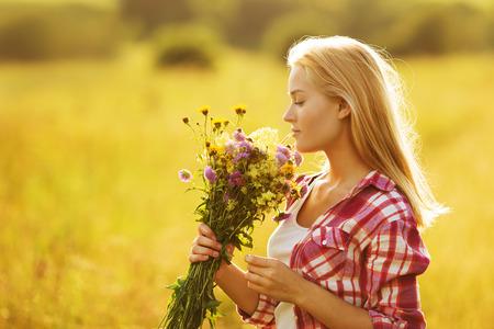 fleurs des champs: Bonne fille blonde avec un bouquet de fleurs sauvages Banque d'images