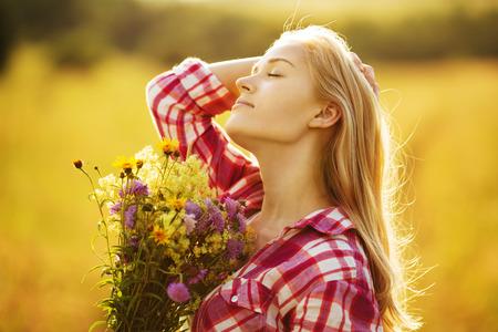 campo de flores: Muchacha hermosa feliz con un ramo de flores silvestres Foto de archivo