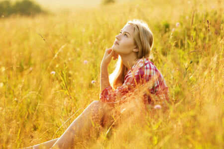 luxuriate: Happy girl sitting on the grass and dreaming