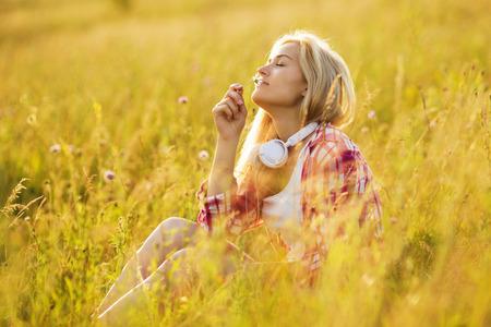 campo de flores: Muchacha feliz con los ojos cerrados oliendo una flor