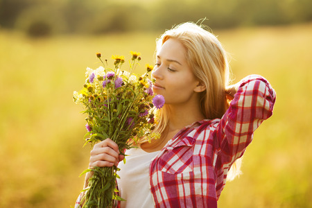 Happy beautiful girl with a bouquet of wildflowers