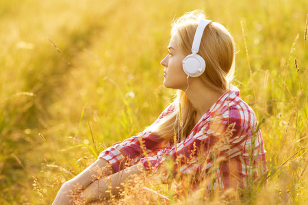 rest and relaxation: Beautiful girl with headphones sitting in the grass