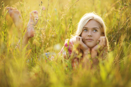 Beautiful happy girl in the grass looking up Imagens