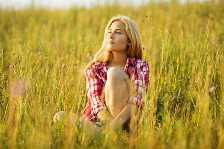 luxuriate: Happy beautiful blonde girl sitting on grass