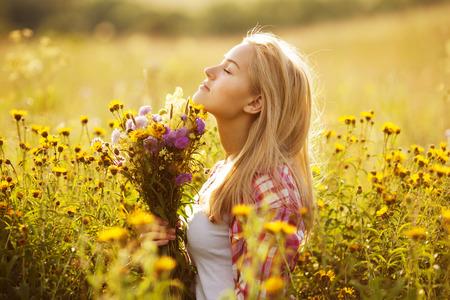 La muchacha rubia hermosa entre las flores silvestres en verano Foto de archivo