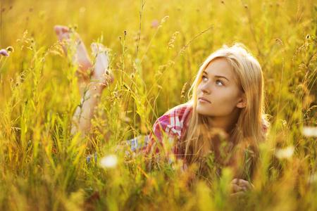 Beautiful blonde girl lying in the tall grass