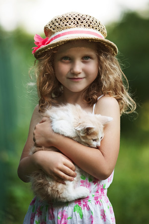 endearment: Happy cute little girl with a kitten