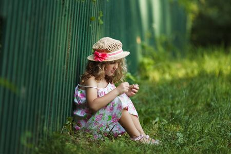 sits: Little girl sits leaning against a fence